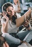 Музыка девушки слушая и тетрадь с прописями читать Стоковая Фотография