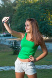 Музыка девушки слушая с наушниками и держать smartphone Стоковое Изображение RF