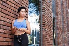 Музыка женщины слушая на smartphone во время jogging Стоковое фото RF