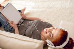 Музыка женщины слушая в наушниках с таблеткой в руках Стоковая Фотография RF