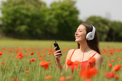 Музыка женщины дышая и слушая в поле Стоковая Фотография