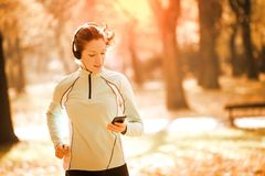 Музыка женщины jogging и слушая стоковое изображение rf