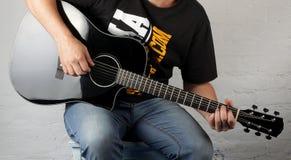 Музыка - игра человека черная электрическая акустическая гитара Стоковое Изображение RF