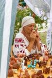 Музыка игр женщины на свистке глины в магазине с сувенирами и игрушками глины на фестивале сыра Adyghe в Adygea Стоковое Фото
