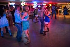 Музыка кантри людей танцуя в сломленном танцевальном зале спицы в Остине, Техасе Стоковые Изображения