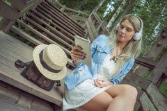Музыка красивой молодой белокурой женщины битника слушая в наушниках в парке с таблеткой в руках, сидя на деревянных шагах Стоковое фото RF