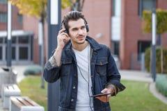 Музыка молодого вскользь человека слушая к осень таблетки Стоковые Фото
