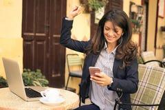 Музыка молодой бизнес-леди слушая на умном телефоне на кафе Стоковые Изображения