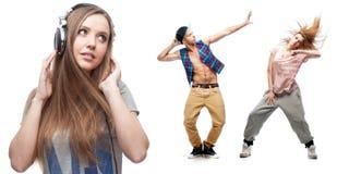 Музыка молодой женщины слушая и 2 танцора на предпосылке Стоковые Фото