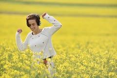 Музыка молодой, эмоциональной и счастливой женщины слушая в наушниках i Стоковая Фотография RF