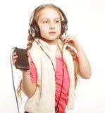 Музыка наушников маленькой девочки танцев поя на белой предпосылке Стоковое Фото