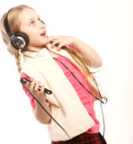 Музыка наушников маленькой девочки танцев поя на белой предпосылке Стоковое Изображение RF