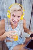 Музыка довольно белокурой женщины слушая с ее мобильным телефоном и выпивая апельсиновым соком Стоковые Изображения