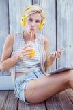 Музыка довольно белокурой женщины слушая с ее мобильным телефоном и выпивая апельсиновым соком Стоковые Изображения RF