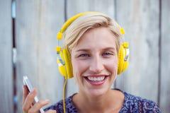 Музыка довольно белокурой женщины слушая с ее мобильным телефоном Стоковые Фотографии RF