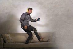 Музыка привлекательного человека слушая онлайн с наушниками и мобильным телефоном играя песню петь Air Guitar и танцевать беспеча стоковые изображения rf