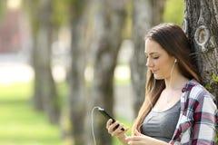 Музыка расслабленной девушки слушая в парке Стоковое фото RF