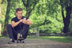 Музыка скейтбордиста слушая от smartphone стоковая фотография rf