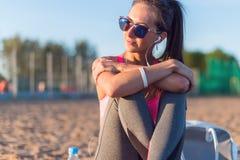 Музыка солнечных очков красивой женщины спортсмена фитнеса нося слушая отдыхая после разрабатывает работать на вечере лета Стоковое Фото