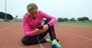 Музыка спортсменки слушая на мобильном телефоне на месте спорт 4k видеоматериал