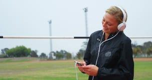Музыка спортсменки слушая на мобильном телефоне на месте спорт 4k сток-видео