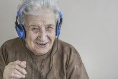 Музыка старшей женщины слушая с наушниками Стоковые Изображения RF