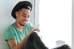 Музыка счастливого африканского человека слушая около окна Стоковое Изображение
