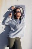 Музыка счастливой женщины слушая в заходе солнца на стене Стоковые Фото