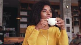 Музыка чашки кофе удерживания молодой женщины слушая на наушниках сток-видео