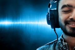 Музыка человека слушая на предпосылке волны стоковое изображение