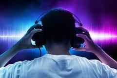 Музыка человека слушая на предпосылке волны стоковое фото rf