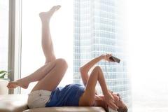 Музыка smartphone молодой женщины слушая в наушниках лежа дальше так Стоковые Изображения