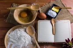 Мука, масло, сахар, яичка, примечания книги, настил Брайна деревянный Стоковое фото RF