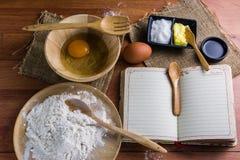 Мука, масло, сахар, яичка, примечания книги, настил Брайна деревянный Стоковые Фото