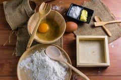 Мука, масло, сахар, яичка, торт с прибором на таблице Настил Брайна деревянный Стоковая Фотография
