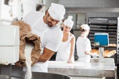 Мука мужского хлебопека лить в замешивая машине стоковая фотография