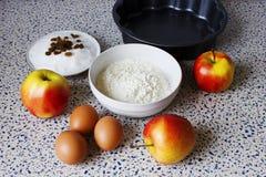 Мука, сахар, изюминки, яичка и яблоки для домодельных печениь Стоковая Фотография