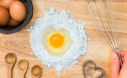 Мука состава взгляд сверху с яичком и ингридиентами для домодельной хлебопекарни на деревянной предпосылке Стоковое Изображение
