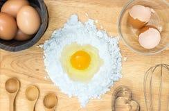 Мука состава взгляд сверху с яичком и ингридиентами для домодельной хлебопекарни на деревянной предпосылке Стоковые Изображения