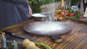 Мука хлебопека лить белая на деревянной доске на кухонном столе, еде и предпосылке овоща Повар шеф-повара брызгая муку видеоматериал