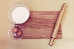 Мука, яичка и вращающая ось на деревянной разделочной доске Стоковое Изображение