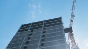 Мульти-этаж под зданием конструкции и кран конструкции на предпосылке ясного неба сток-видео