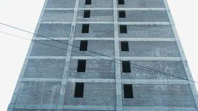 Мульти-этаж под зданием конструкции и кран конструкции на предпосылке ясного неба акции видеоматериалы