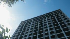 Мульти-этаж под зданием конструкции и кран конструкции на ясной предпосылке неба видеоматериал