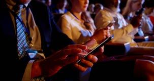 Мульти-этнические бизнесмены используя мобильный телефон во время семинара дела в аудитории 4k