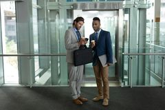 Мульти-этнические бизнесмены обсуждая над мобильным телефоном около лифта стоковое фото rf