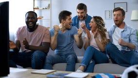 Мульти-этнические друзья празднуя цель, наблюдая футбол дома, единение стоковое фото rf