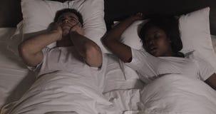 Мульти-этнические пары лежа в кровати совместно Человек страдает от его партнера храпя в кровати Соедините образ жизни и людей сток-видео