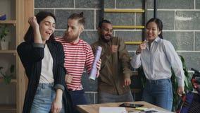 Мульти-этнические start-up коллеги дела имеют танцы потехи в офисе просторной квартиры и успех праздновать проекта видеоматериал