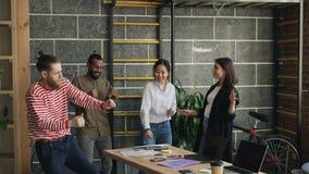 Мульти-этнические start-up коллеги дела имеют танцы потехи в печатных документах современного офиса бросая и праздновать сток-видео